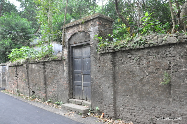 A huge derelict wooden door in another wall of the Rajbari on the main Taki road at Taki, West Bengal, India by Gautam Lahiri