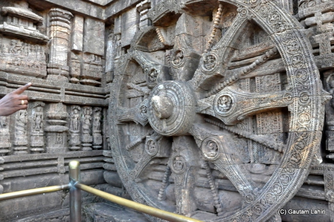 One of the twenty four wheels that adorn the temple base, the interval between each spoke is three hours and each beaded rod is ninety minutes apart and by placing the index finger on the wheel hub, and looking at the falling shadow, the bead which gets the shadow tells the time of the day  at Puri, Odisha, India by Gautam Lahiri