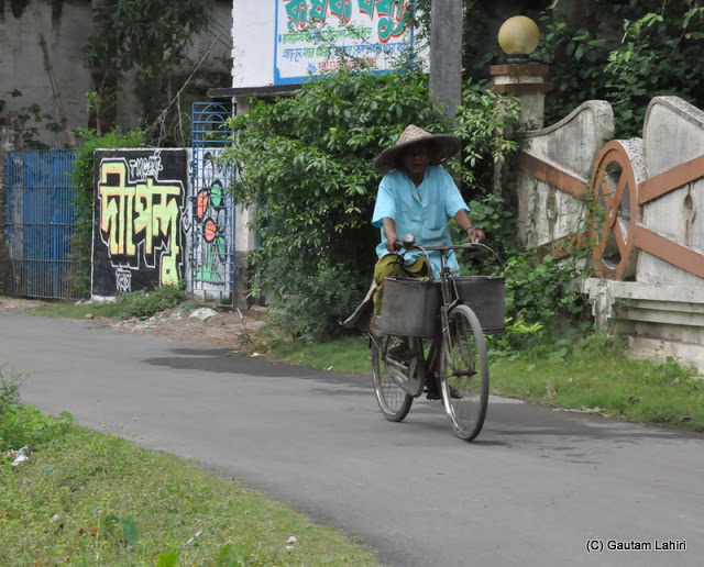 A milkman with a makeshift hat on a bicycle starts his day to provide personalized service at Taki, West Bengal, India by Gautam Lahiri