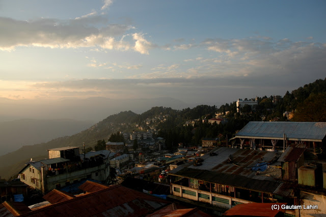 Along the hill edge as we walked, the town with its small and conical houses draped the hill surface ..all under the glare of the morning sun  at Darjeeling, West Bengal, India by Gautam Lahiri
