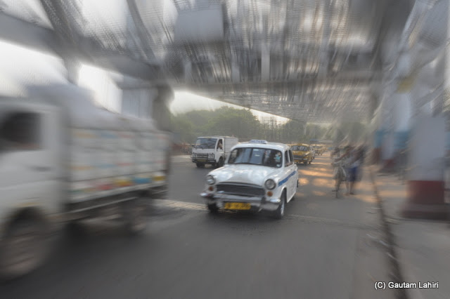 The Calcutta 'Taxi' the good old Ambassador proudly drives over the Howrah bridge. Kolkata is incomplete without a ride in this car at Kolkata, West Bengal, India by Gautam Lahiri