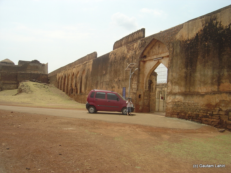 We were parked in front of the Gagan Mahal. Instead of the leashed and restless horses, stood the red Wagon R. The arched gateway gave way to an opening that was well maintained with a green bush that complemented the blue sky above at Bidar fort by Gautam Lahiri