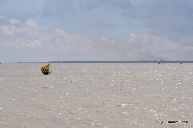 A small fishing boat sets off from the banks of river Ganges at Diamond Harbor, West Bengal, India by Gautam Lahiri