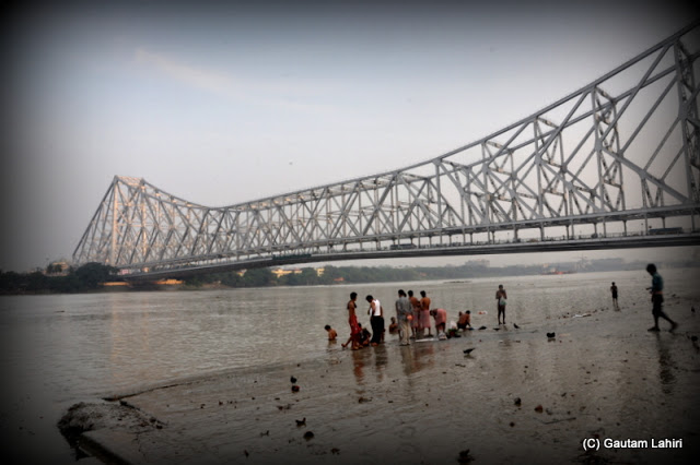 Bathers walk over the muddy banks of the river, ready to take a dip in the cool waters of the river Hooghly  at Kolkata, West Bengal, India by Gautam Lahiri