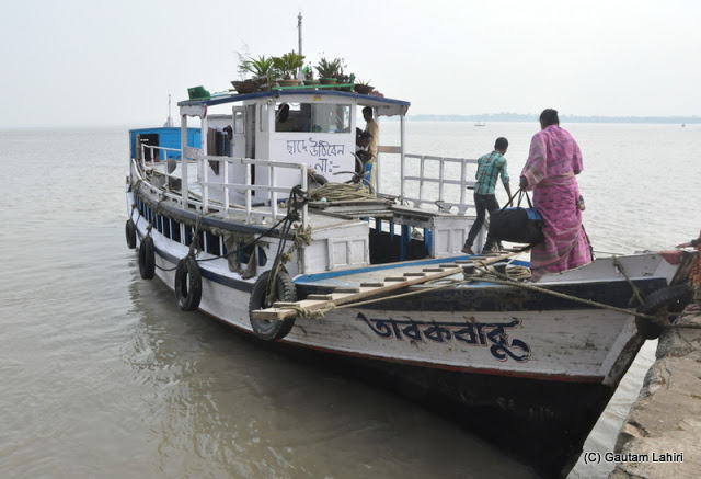 Passengers over the deck making their way into the sitting compartment on Rupnarayan river at Gadiara, Hooghly, West Bengal, India by Gautam Lahiri