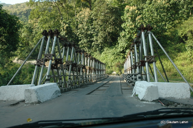 A wooden bridge awaiting the weight of our vehicle as I aligned the car to cross a stream  at Darjeeling, West Bengal, India by Gautam Lahiri