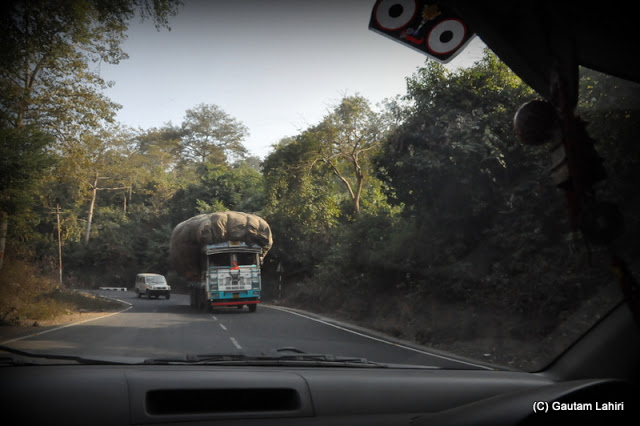 A heavily loaded truck comes straight for our car through the winding roads  at Massanjore, Jharkhand, India by Gautam Lahiri