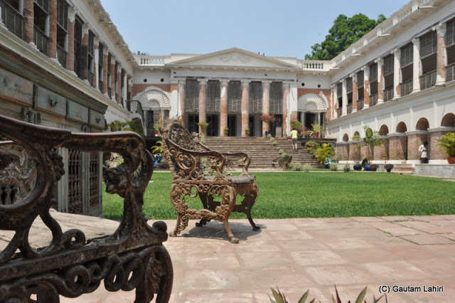 A view from the left. A finely manicured grass centers as Greek styled pillared halls encircle on either side at Bawali Rajbari, Kolkata, West Bengal, India by Gautam Lahiri