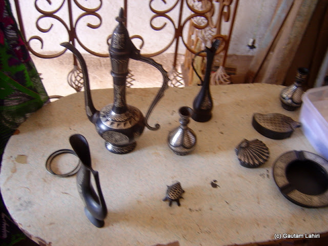 Bidriware objects lay displayed in front of us - Water decanter, ashtray, plaques, and there stood the wine decanter in Bidar by Gautam Lahiri
