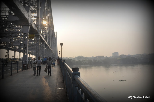 The smoke and fog enveloped the city limits, while the Howrah bridge stood tall and gallant ushers the sun and the new day  at Kolkata, West Bengal, India by Gautam Lahiri