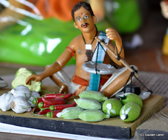 A vegetable seller showing exquisite detailing..even the weight on the left platter pulling down the balance is shown, truly realistic at Krishnanagar, West Bengal, India by Gautam Lahiri