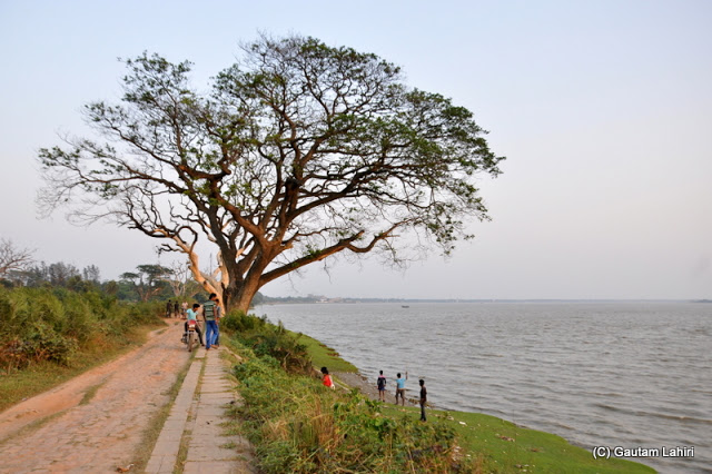 The un-motorable road by the river bank. The river takes a slow right turn and extends further to meet the sea at Bawali Rajbari, Kolkata, West Bengal, India by Gautam Lahiri