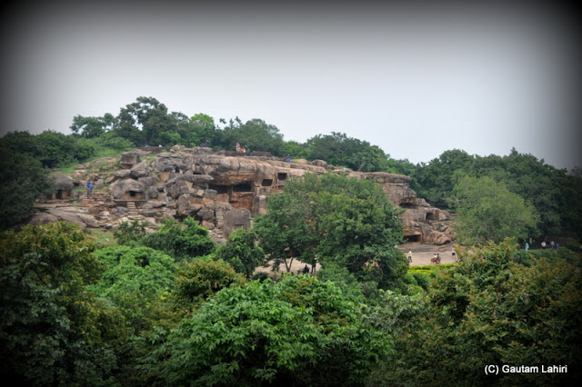 We were seeing the Udayagiri rock caves from Khandagiri hill, entombed in its rocky layers amidst trees  at Bhubaneshwar, Odissa, India by Gautam Lahiri