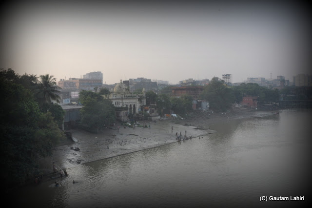 The muddy bank and the river water sweeping over the temples which are standing in unison for not less than 200 years  at Kolkata, West Bengal, India by Gautam Lahiri