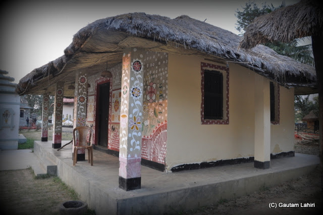 A tribal cottage on display looked cozy enough, and tempted visitors to step in to enjoy the warmth from the hay stacked roof  at Santiniketan, West Bengal, India by Gautam Lahiri