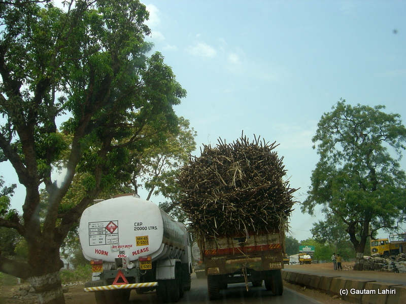 A long fuel tanker is seen overtaking from the left as it passes a trailer loaded with sugarcane. The trailer was already listing on its springs by about ten degrees. I did not dare to overtake or follow the tanker. If the sugarcane topples, we would be pasted across the carpet road in no time from Hyderabad to Bidar by Gautam Lahiri