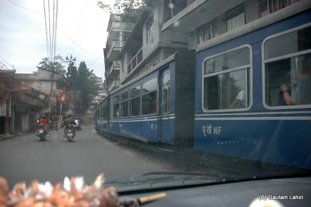 The Darjeeling toy train and our car playing hide and seek on the Hill Cart Road  at Darjeeling, West Bengal, India by Gautam Lahiri