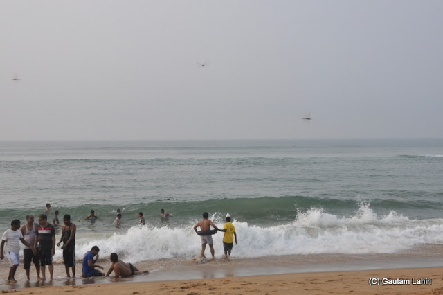 Waves splash, people float on rubber tubes and the day brightens making all of us stay in the water forever  at Puri, Bhubaneshwar, Odisha, India by Gautam Lahiri