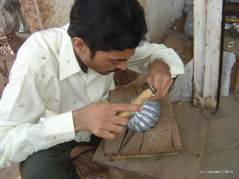 Artisans using simplest of the tools, as we see here, a light hammer and chisel to carve out metal ornamentation on Bidriware at Bidar by Gautam Lahiri