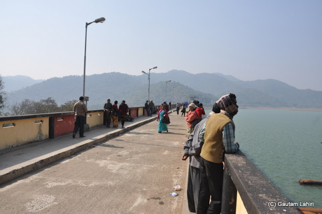 The visitors taste the cool breeze over the dam as we walk past them  at Massanjore, Jharkhand, India by Gautam Lahiri