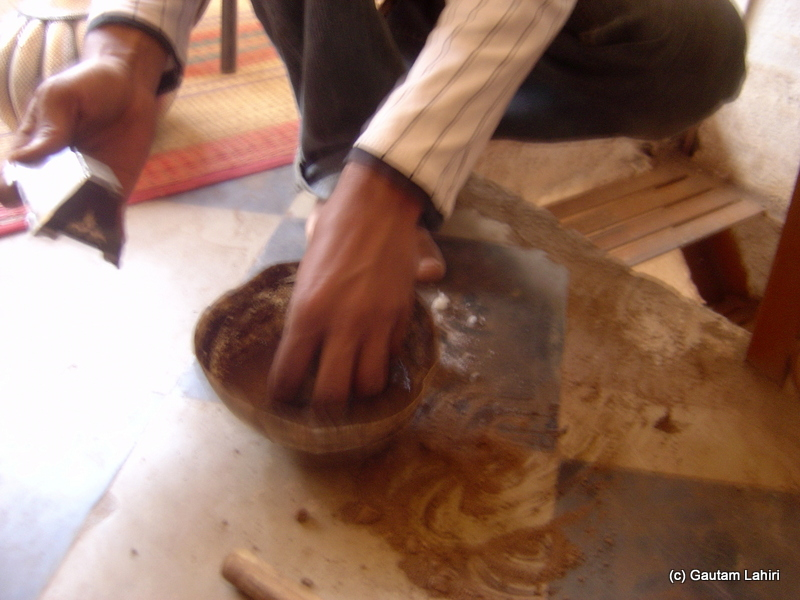 Kaseem applying the soil with a mix of water in it. The object on his left-hand gets its touch and started to lighten up the mundane room with its ageless glow at Bidar by Gautam Lahiri