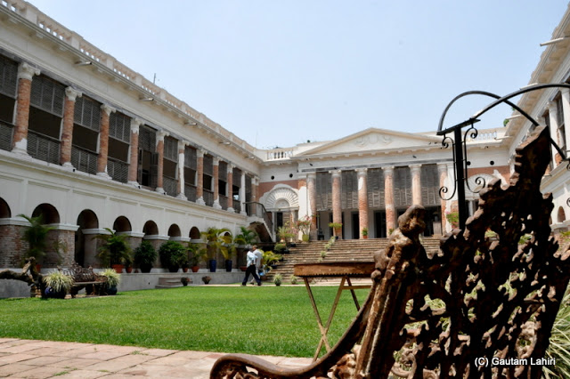 A old wrought iron chair perhaps stand testimonial to a 300-year-old palace as it overlooks the Greek styled building at Bawali Rajbari, Kolkata, West Bengal, India by Gautam Lahiri