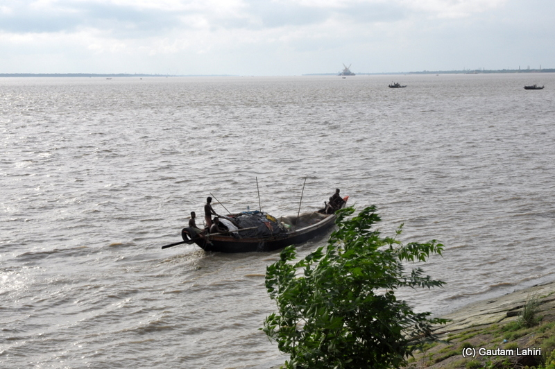 A boat spears away through the Hooghly water as the late afternoon wind drives everything away at Diamond Harbor, West Bengal, India by Gautam Lahiri