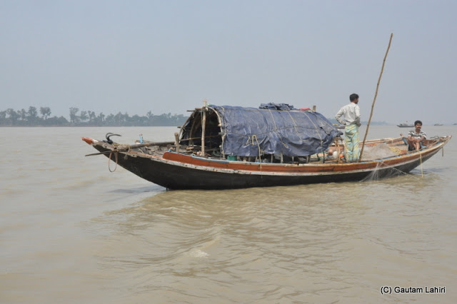 This boat had its net strung across the water and sweeping the depths below in anticipation of fishes getting trapped in the net at Gadiara, Hooghly, West Bengal, India by Gautam Lahiri