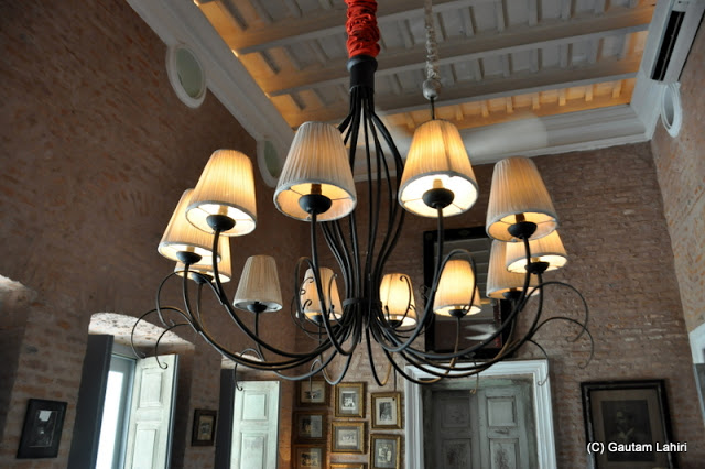 A chandelier puts in a mild glow around the dining room along with the daylight filtering through the glass doors at Bawali Rajbari, Kolkata, West Bengal, India by Gautam Lahiri