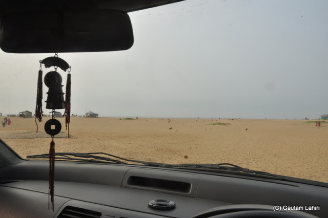 Through the tinted windscreen of the car, the wide expanse of the shimmering sand looked like a forbidden territory of quicksand  at Puri, Bhubaneshwar, Odisha, India by Gautam Lahiri