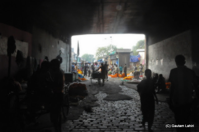 The road made of stone bricks, under the Howrah bridge..looked sinister with its black and white hues with only the flowers like islands of color  at Kolkata, West Bengal, India by Gautam Lahiri