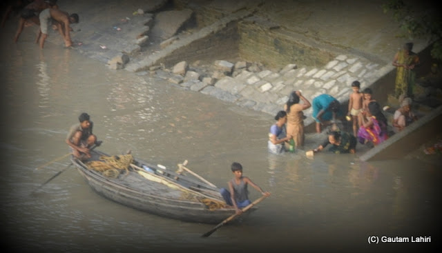 A lone boat loaded with fishing net skirts the river bank as early morning bathers take a holy dip  at Kolkata, West Bengal, India by Gautam Lahiri