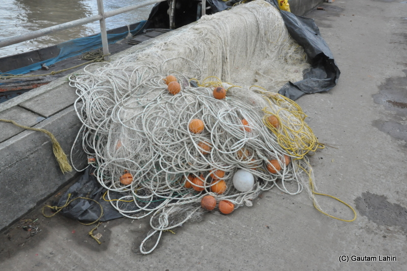 Fishing nets remained coiled up on the harbor floor at Diamond Harbor, West Bengal, India by Gautam Lahiri