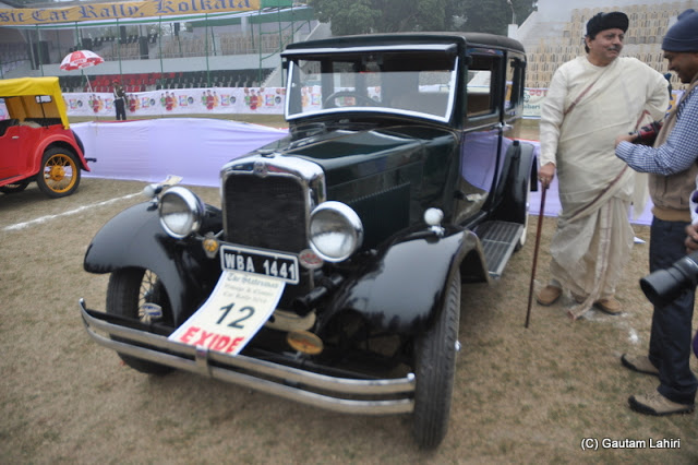 The owner of this 1926 Studebaker Erskine is dressed in the attire of those years and waits to start her 29.6 HP, 6 cylinder engine  at Kolkata, West Bengal, India by Gautam Lahiri