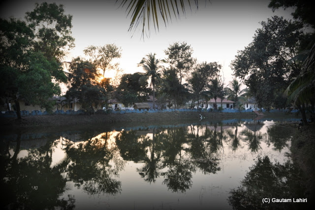 A line of tribal villages along a pond as the setting sun peeping over the trees  at Santiniketan, West Bengal, India by Gautam Lahiri