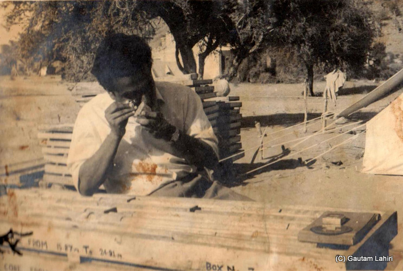My father, examines intently, rock and cartographic samples at Degana, Rajasthan, India beside a tent by Gautam Lahiri