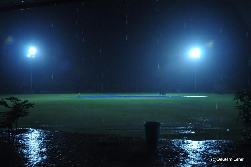 The floodlights glow under the driving rain on a cricket field by Gautam Lahiri